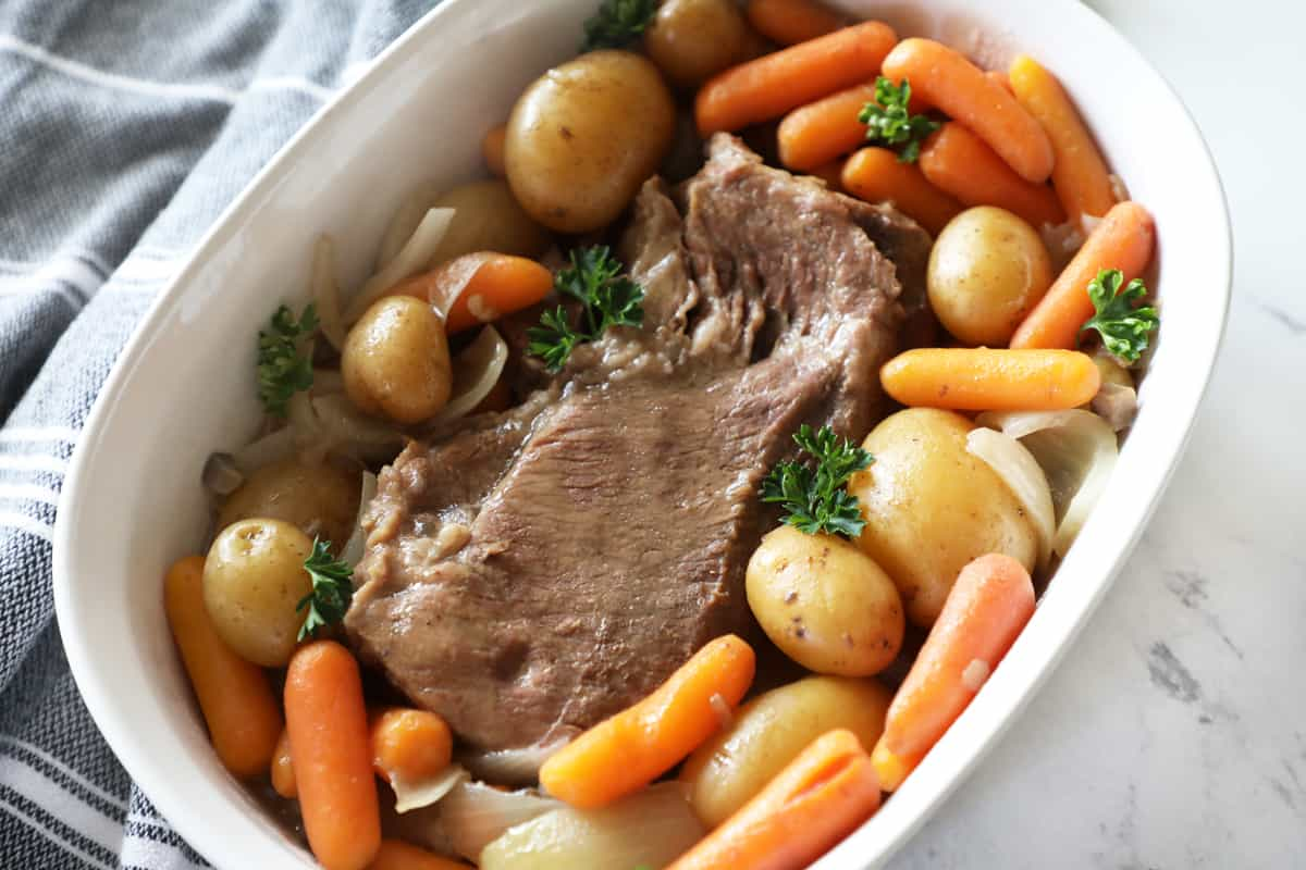 close up of slow cooker pot roast garnished with fresh parsley