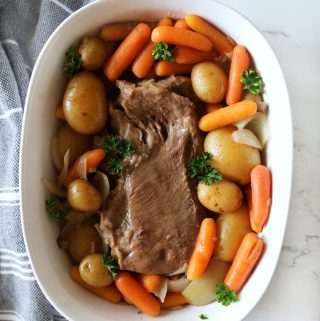 close up of a roast in a white dish with fresh parsley garnish