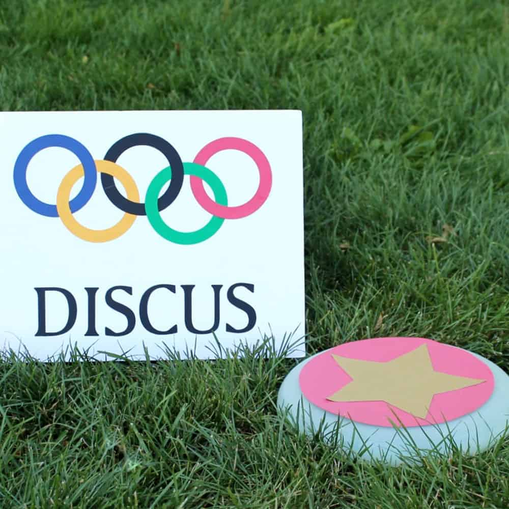 Discus made from a frisbee on the grass with an olympics sign