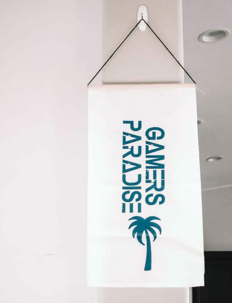 white hanging banner that says Gamers Paradise with a palm tree