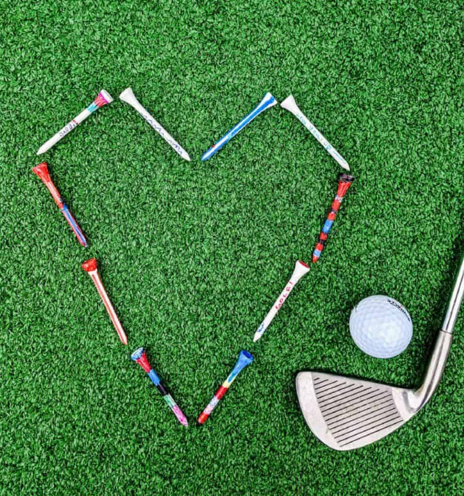 Golf tees painted with sharpies and forming a heart shape on golf turf