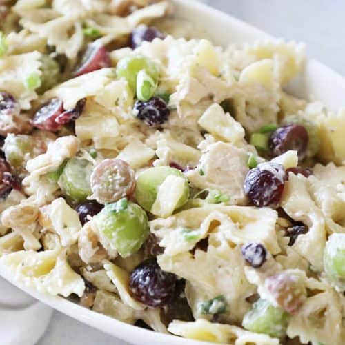 ranch pasta salad in a white bowl with green and purple grapes