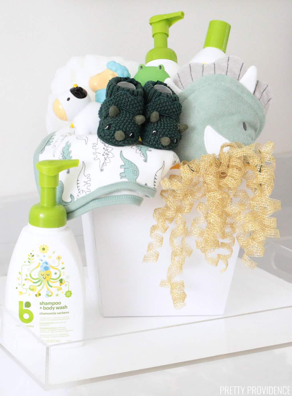 Baby Shower Gift basket with dinosaur towels, green dinosaur slippers, bath toys, baby shampoo and lotion