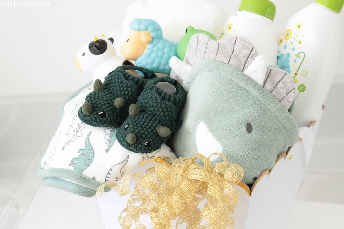 Baby shower gift basket with dinosaur bath towels, knit booties, toys and baby shampoo