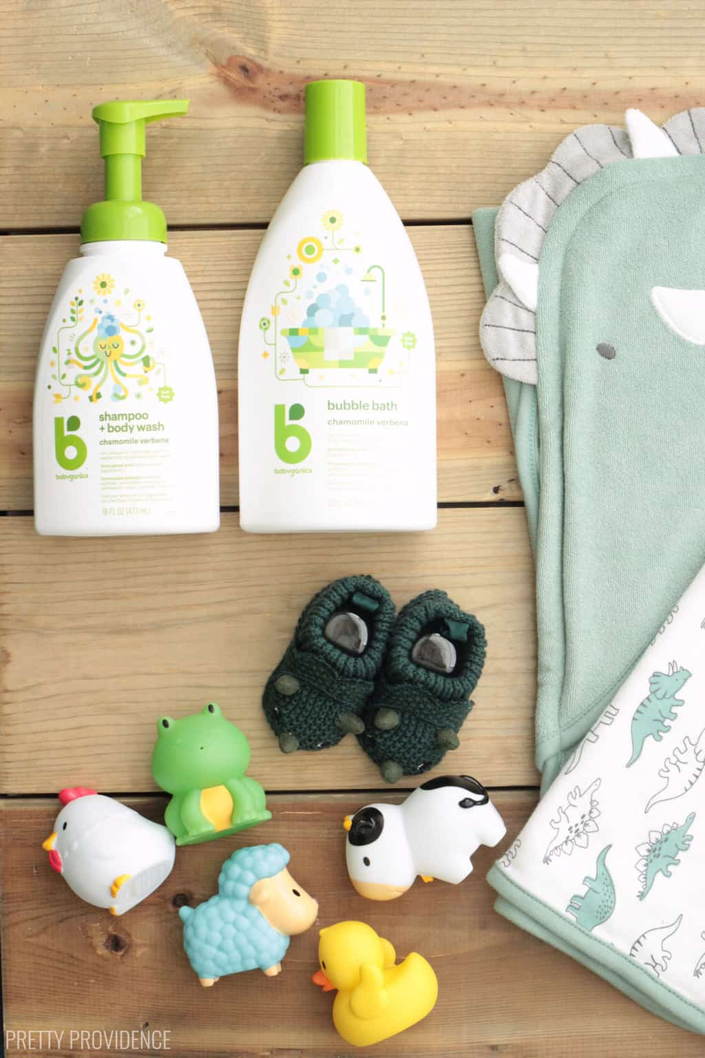 baby shower gift items: dinosaur towels, green dinosaur slippers, bath toys, baby shampoo and lotion