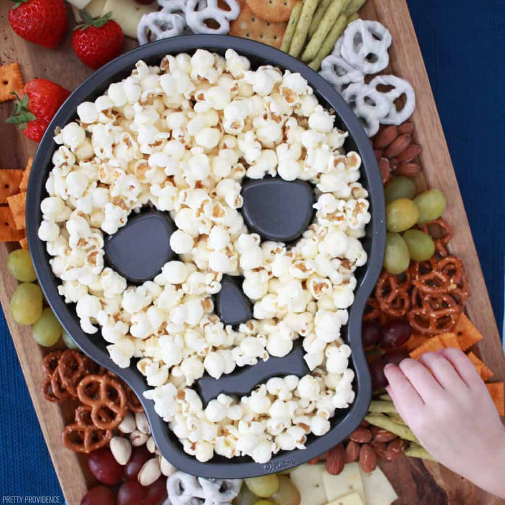 Halloween charcuterie board with a skull cake pan full of popcorn