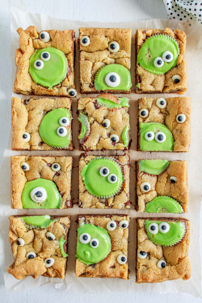 Monster Peanut Butter Cookie bars with green reeses and candy eyeballs