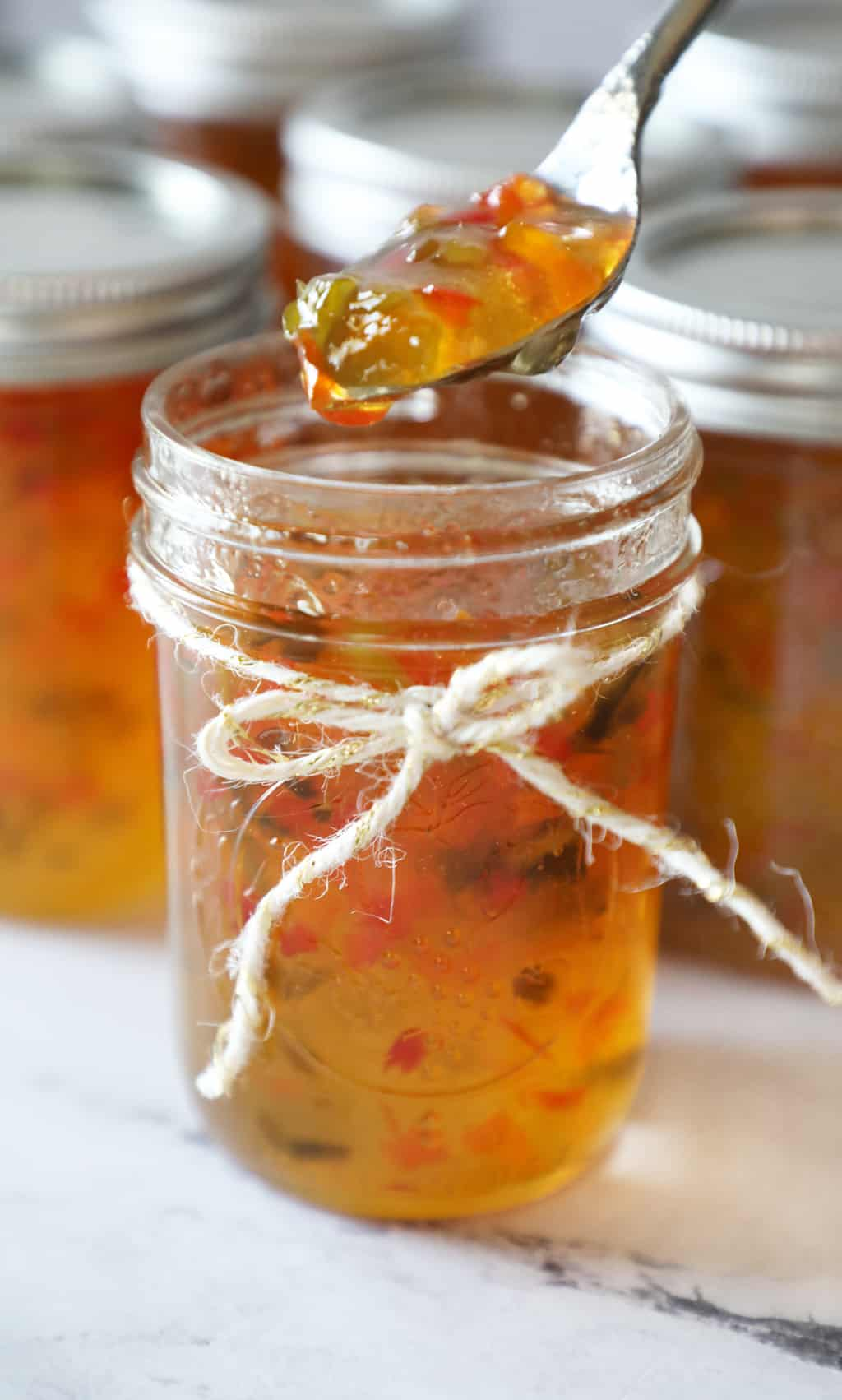 a jar of pepper jelly tied with twine with a spoon with jelly hovering above it