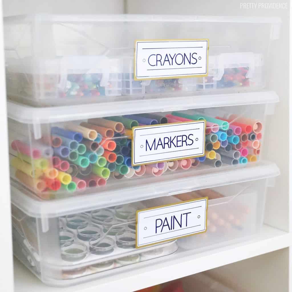 Trois bacs transparents contenant des marqueurs, de la peinture et des crayons, avec des étiquettes blanches