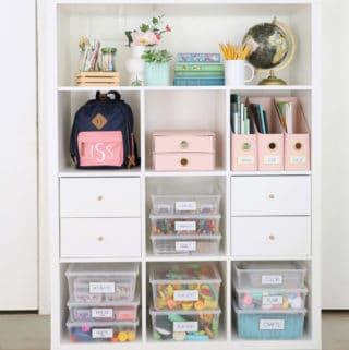 art supplies organized and labeled on a white IKEA kallax shelf