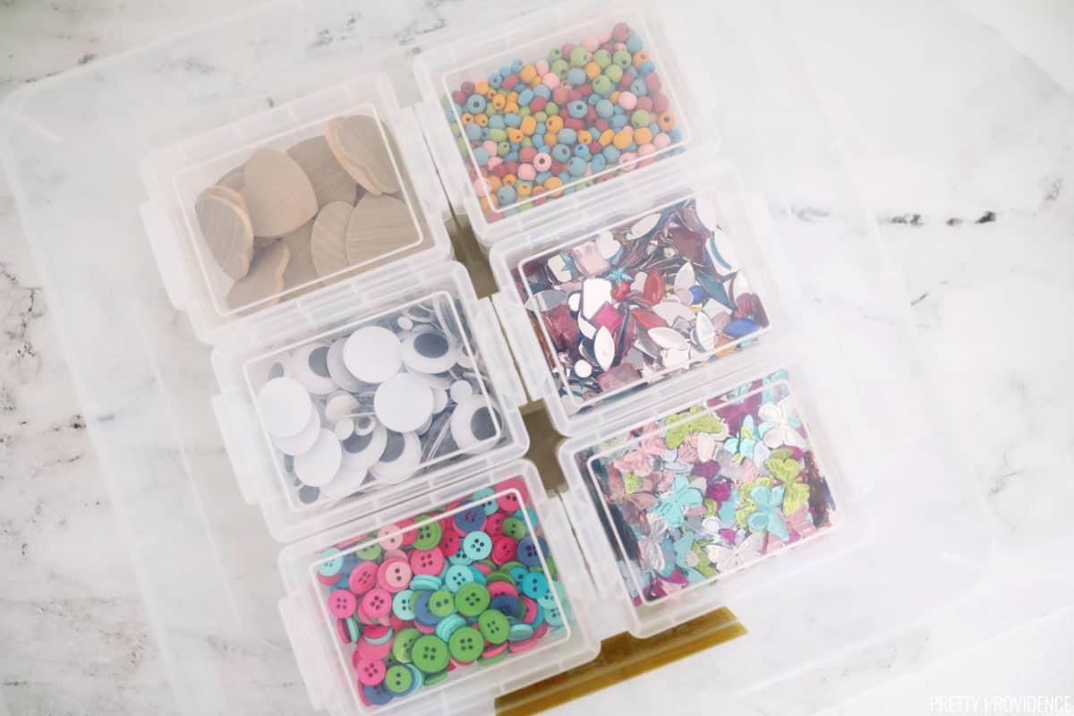 Petites fournitures d'artisanat dans des bacs transparents organisés dans un bac plus grand