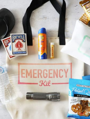 a canvas bag that says emergency kit on it with items surrounding it