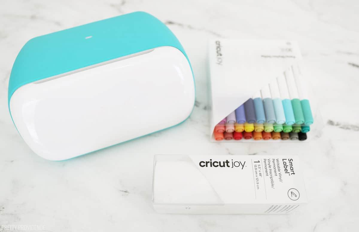 Machine Cricut Joy, vinyle inscriptible Cricut et stylos Cricut joy sur une surface en marbre