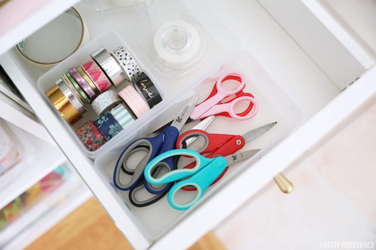 Ciseaux, ruban washi et scotch soigneusement organisés dans un tiroir blanc
