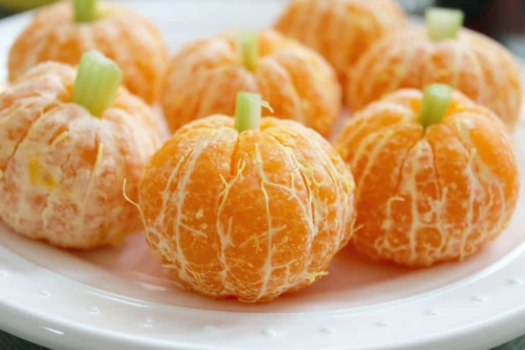 Clementines made to look like pumpkins with green stems