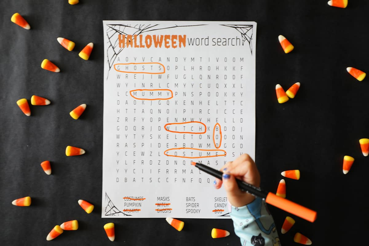 a little one's hand with an orange marker filling out a printable Halloween word search