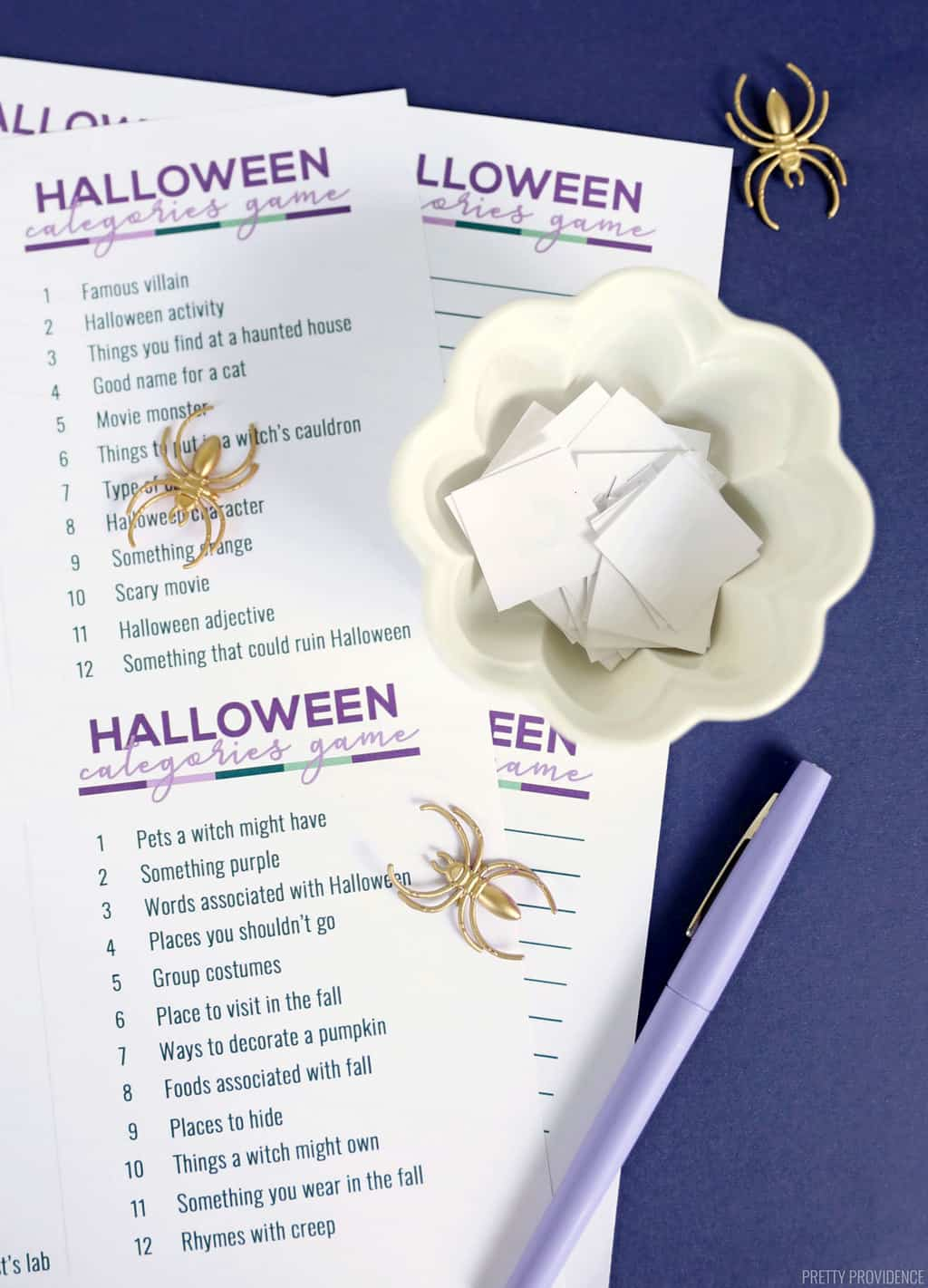 Printed scattergories lists with gold spider toys and a bowl of cut-out paper