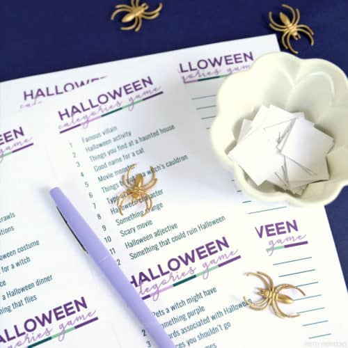 Halloween scattergories game with a purple marker, gold spiders and a bowl with white squares of paper in it