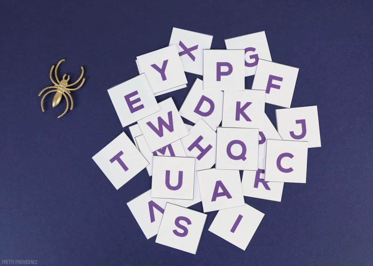 White squares with letters of the alphabet on them on a navy blue background and one gold spider