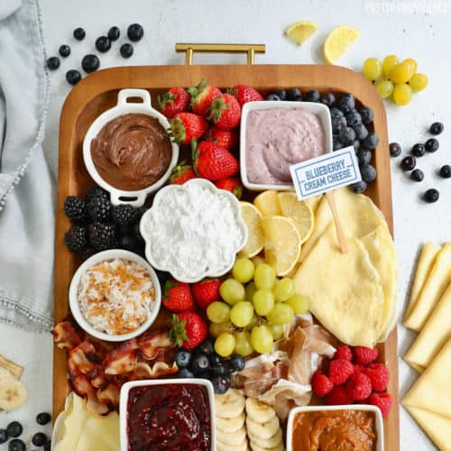 Breakfast charcuterie board with crepe toppings, fruit, spreads, bacon and powdered sugar