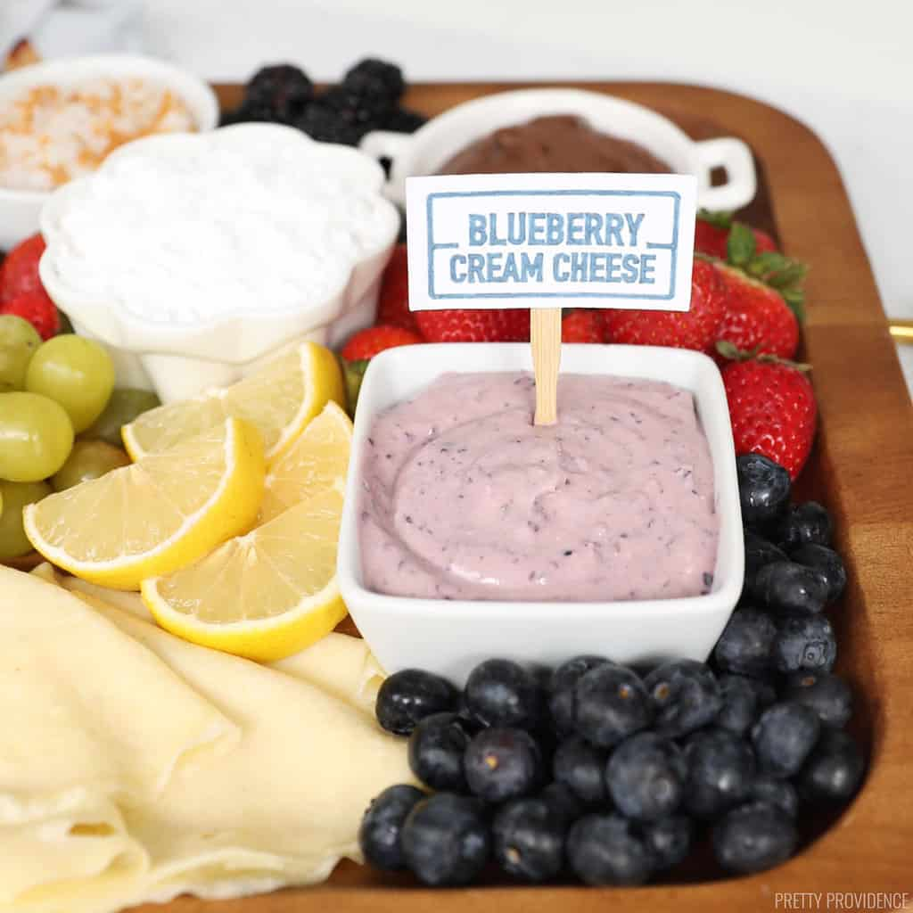 food label made from card stock that says 'blueberry cream cheese' on a wood stick in a small bowl of cream cheese, surrounded by berries and crepe toppings