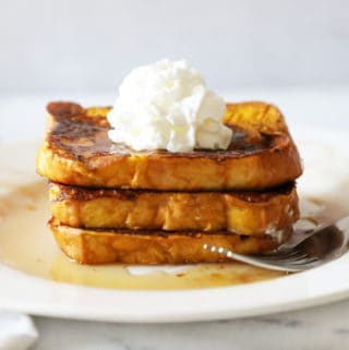 three slices of pumpkin French toast stacked on a white plate