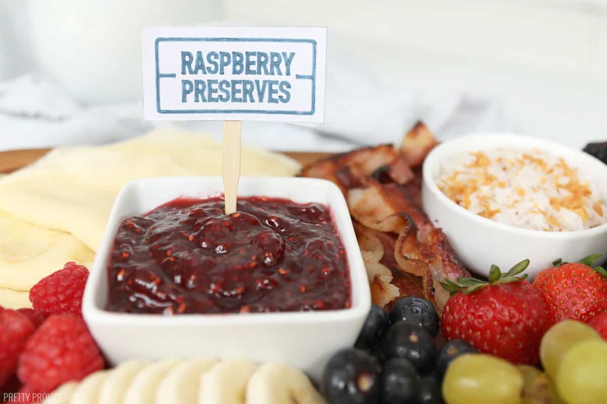 Raspberry preserves in a small bowl with a label sticking out of it, surrounded by fruit